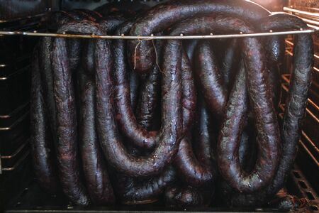 Homemade sausages of wild beaver, smoked sausage, game dish of russian cuisine. Drying in a oven