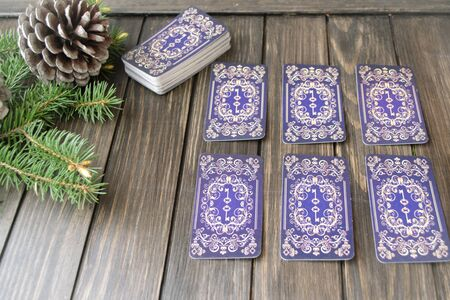 Concept of Christmas divination predictions on tarot cards, wooden black background Reklamní fotografie