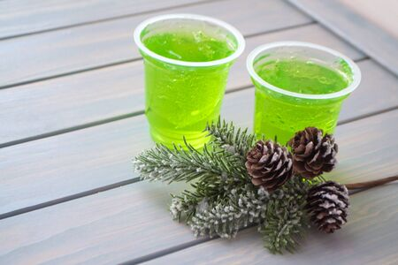 green apple jelly on a small glass on wooden planks table