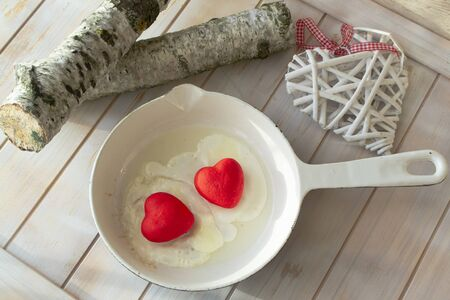 Valentine breakfast. Love funny food on the pan. Two red hearts with scrambled eggs Conceptual love card, top view image Banco de Imagens