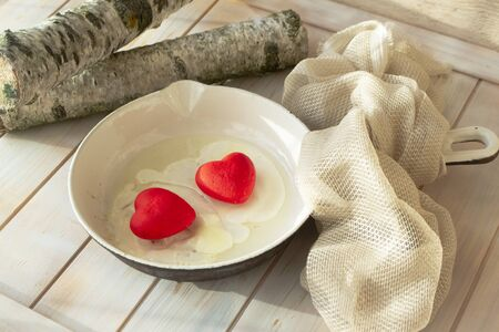 Conceptual lova card image, valentines day breakfast. Love funny food on the pan. Two red hearts with eggs. Shabby table