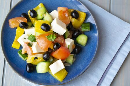 Greek salad with feta cheese and sun-dried olives on blue wooden table and blue plate