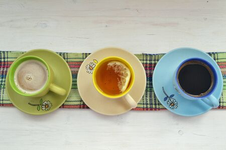 cup of coffee, tea and cappuccino in colorful cups