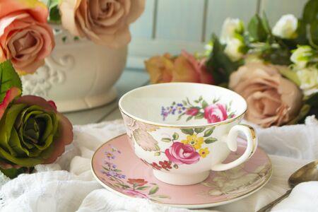 Vintage tea cup, frame of pastel roses flowers