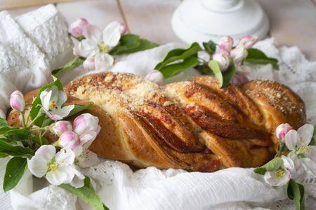 Pain sucré traditionnel en osier aux fraises. Petit pain de blé doux sur un fond en bois et des fleurs de printemps. Style rustique. Banque d'images