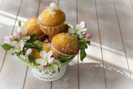 Small freshly muffins in lace wicher basquet and spring flowers on shabby table, copy space