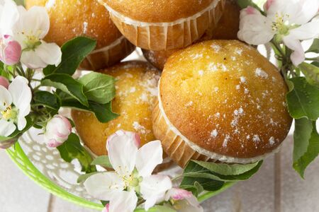 Small golden muffins closeup. Baking decorated with apricot or apple flowers.