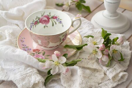 pink vintage afternoon tea party, tea cup and tender flowers on wooden tray and lacy tablecloth