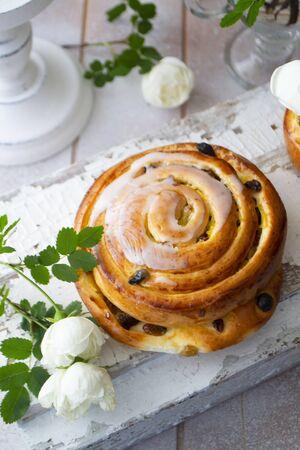 Cinnamon bun swirled with raisins, vintage and shabby style, vertical image