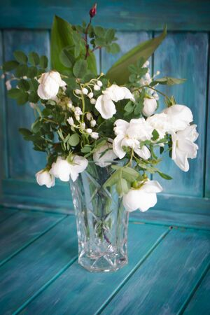 A wedding bouquet of lilies of the valley and white roses. Teal wooden background Archivio Fotografico