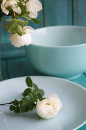 Romantic table setting with bouquet of roses, dishware, on holiday teal table.