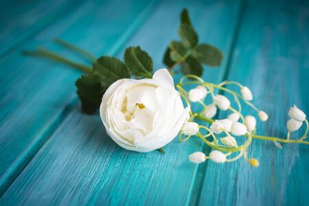 Romantic white bouquet with tender rose tree and lilly of the valley flowers, teal wooden background.