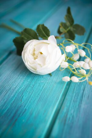 White flower on teal blue wooden table. A bouquet of white roses and lillies of the valley