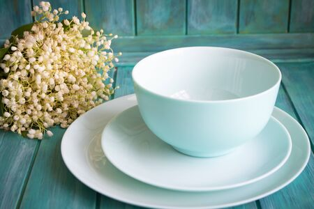Vintage table setting with bouquet of lilies of the valley, empty dishes in teal color