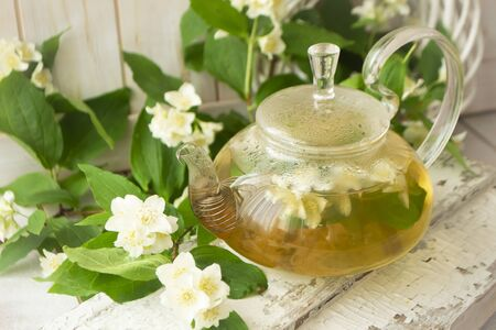glass teapot with hot tea and jasmine flowers. branches of blooming jasmine. Archivio Fotografico