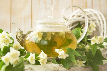 glass teapot with hot tea and jasmine flowers. Closeup Archivio Fotografico