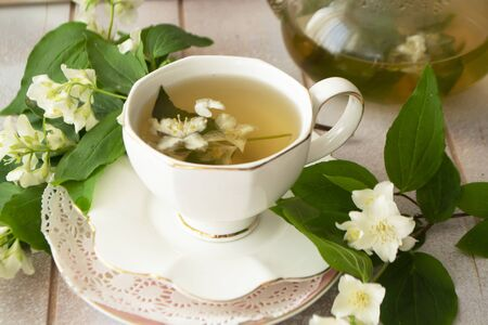 vintage mug of herbal tea and jasmine flowers on a white wooden table and jasmine flowers