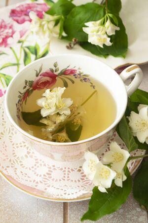 Vintage cup of hot green tea with jasmine flavor and fresh jasmine flowers. Vertical image Archivio Fotografico