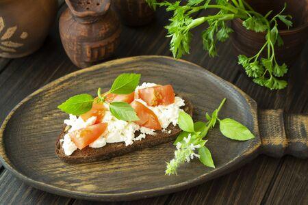 Bruschetta with fresh ricotta cheese, basil, red tomato on dark wooden board
