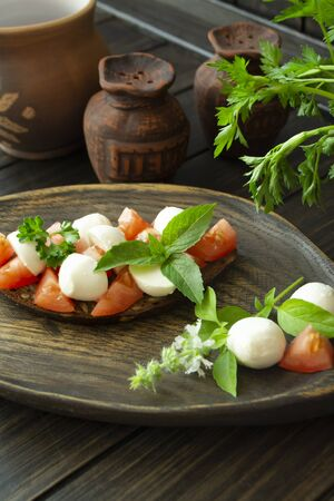Bruschetta with red tomatoes, mozzarella cheese and basil on a old rustic dark table. Vertical image