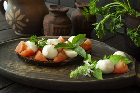 Bruschetta with tomatoes, mozzarella and basil. Traditional italian appetizer or snack