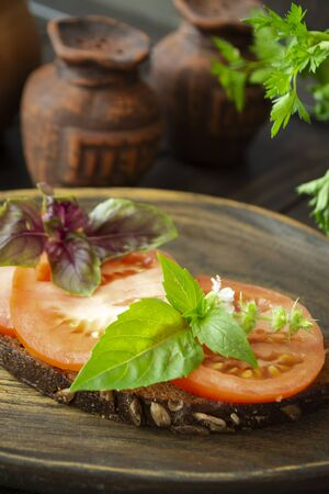 Dark bread bruschetta with red tomatoes and green basil leaves close up on a wooden textured rustic plate. Vertical image