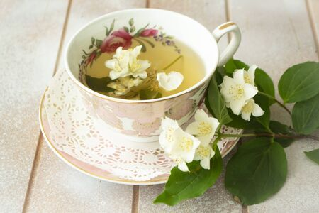 A cup of green tea with jasmine flowers. Fresh jasmine branches. Vintage classic cup Archivio Fotografico