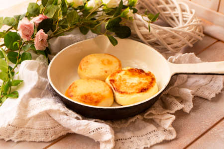 Baked fried cottage cheese pancakes in a white vintage pan Archivio Fotografico
