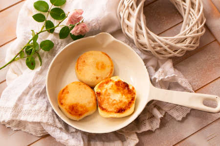 Cast-iron frying pan with curd pancakes or syrniki, shabby table, top view Archivio Fotografico