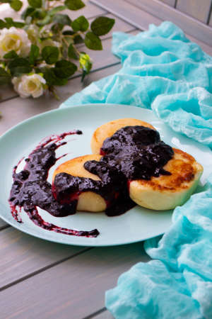 Cottage cheese pancakes with currant and blubbery jam on vintage teal plate Archivio Fotografico