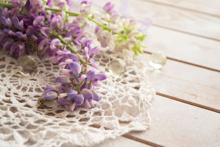 lovely lupine and vintage lace on rustic white wooden background in light, floral greeting card.