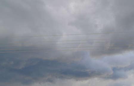 Electricity transmission power lines, high voltage lines. Storm clouds in dark danger sky