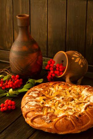 Apple and rowan pie on dark wooden background