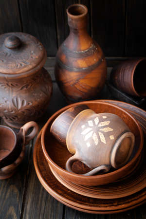 Many empty brown clay bowls and plates on old textured wooden table. Traditional culture about ceramics, pottery, handycraft, handmade kitchenware from natural material