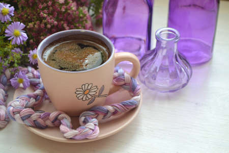 Hot dark coffee in a vintage cup and on an old white wooden background with violet flowers and purple bottles