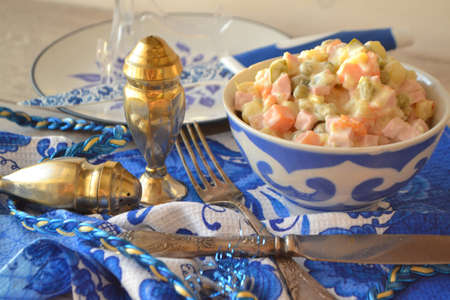 Russian cuisine: salad Olivier in blue and white bowl in gzhel style.