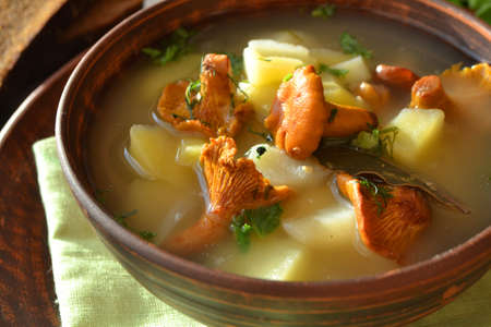 Background of cream soup with chanterelles and fresh thyme. Close up