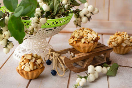 Homemade peanut muffins with white berries on decoration on shabby wooden table Stockfoto