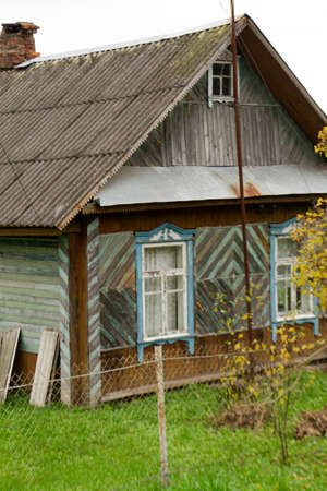 Old traditional wooden house with slate roof in village, Belarus. Vertical image