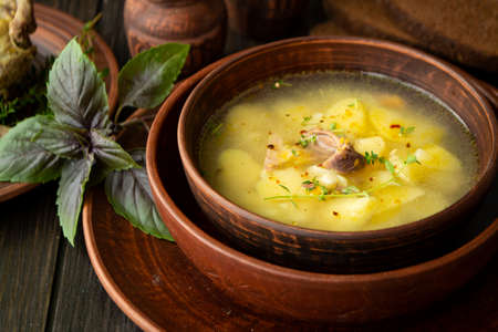 Horseradish soup with wild partridge in a brown vintage bowl. Russian cuisine