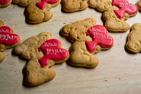 brown gingerbread cookies in the shape of bears with red hearts Stockfoto