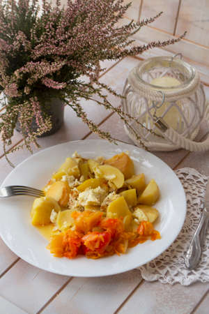 boiled potatoes with peper salad on the white plate, shabby wooden table