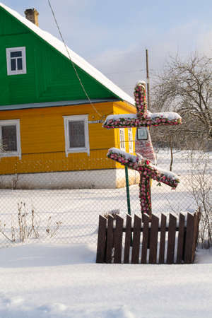 Old wooden cross standing at the crossroads in a village, Belarus. Old Christian orthodox tradition. Vertical image
