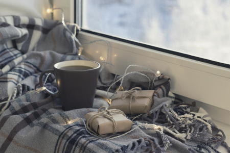 Cup, lights, christmas gifts in craft paper, grey plaid on the window sill. Close up
