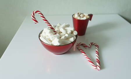 Christmas background, greeting card with a Cup of coffee or hot chocolate with marshmallows, a red plate and candy canes. Holiday photo. The mood of the expectations of celebration