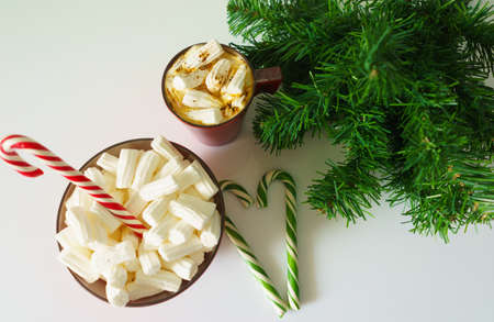 Christmas background, greeting card with a Cup of coffee or hot chocolate with marshmallows, a red plate, candy canes and tree branches. Holiday photo. The mood of the expectations of celebration Stock Photo