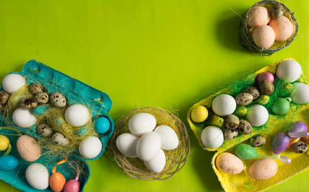 White chicken Chicken and quail eggs in colored paper eco-friendly packaging with decorative sisal. Close-up photo, macro.  Easter background. Food concept