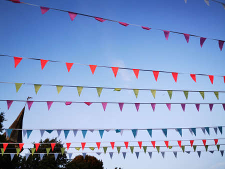 Flags garland for fun festa party event, summer holiday farm feast celebration, carnival. Multi-colored pennant, flags on the rope, festive decoration. Stock Photo