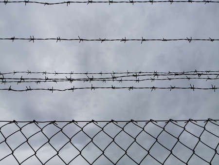 Barbed wire and mesh fence against the sky. Stock Photo