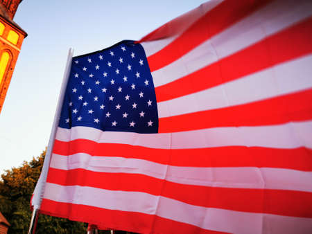 The fabric flag of the United States of America flutters in the wind.